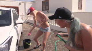 Two topless girlfriends are washing the car and sunbathing on the hood