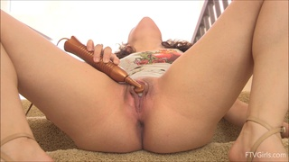 Pretty brunette pleasures her pussy with a vibrator on the stairs