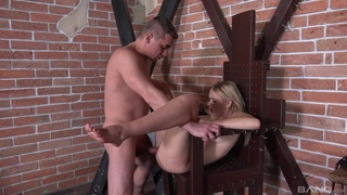 Dom uses bondage furniture in the dungeon during session with biddable babe