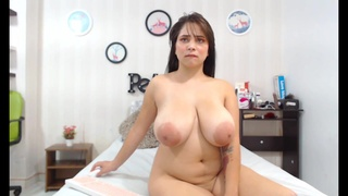 Flexible chick licks her own hanging boobs